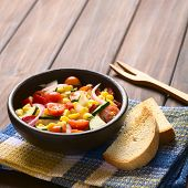 picture of sweet-corn  - Bowl of fresh vegetable salad made of sweet corn cherry tomato cucumber red onion red pepper chives with toasted bread on the side photographed on dark wood with natural light  - JPG