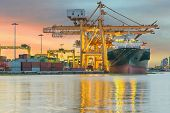 stock photo of ship  - Industrial Container Cargo freight ship with working crane bridge in shipyard at dusk for Logistic Import Export background - JPG