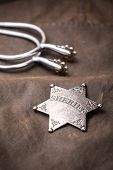 picture of spurs  - Sheriff badge and spurs on brown background - JPG
