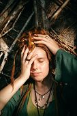 stock photo of dreadlocks  - Close up Pretty Young Woman with Dreadlocks Blond Hair Covering her One Eye While Lying on Sticks - JPG