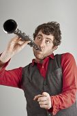 picture of clarinet  - Silly man plays clarinet one handed while pointing at the audience - JPG