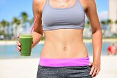 stock photo of smoothies  - Healthy lifestyle fitness woman drinking green vegetable smoothie juice after running exercise - JPG