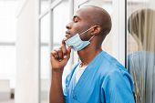 picture of african mask  - Side view of young African doctor in blue uniform taking off surgical mask and keeping eyes closed while leaning at the glass door - JPG