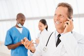 stock photo of people talking phone  - Cheerful mature doctor talking on the mobile phone and gesturing while his colleagues talking in the background - JPG