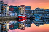 picture of galway  - morning view on row of buildings and fishing boats in Galway Dock with sky reflected in the water HDR image - JPG