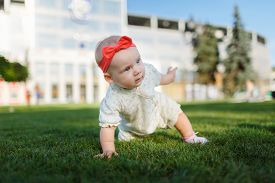 picture of crawl  - Happy babyHappy baby posing in front of a beautiful building in the city park - JPG