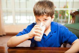 picture of tween  - Blond tween enjoying a glass of milk for breakfast at home - JPG