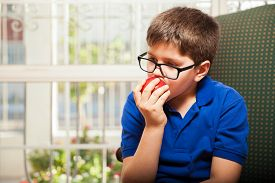 foto of tween  - Blond tween with glasses relaxing at home and biting and apple - JPG