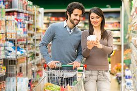 image of grocery cart  - Young couple shopping in a supermarket - JPG