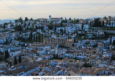 Panoramic view of city of Granada and its outskirts with distant mountains at sunset