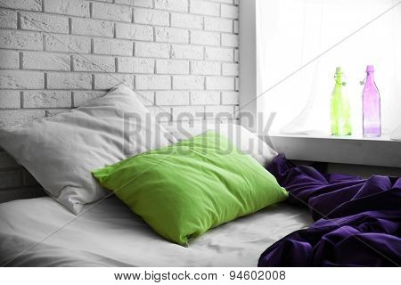 Comfortable bed with green pillow and purple blanket  in bedroom