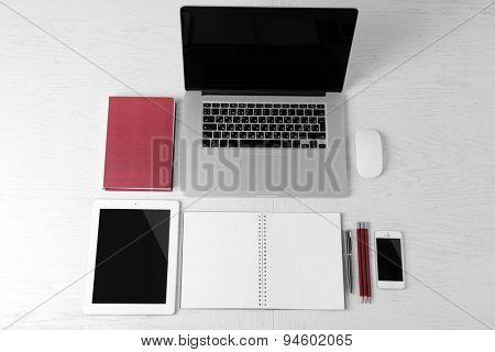 Office supplies and gadgets on white table, top view