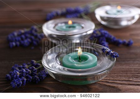 Spa still life with candlelight and fresh lavender on wooden table, closeup