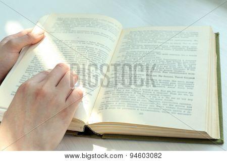 Woman reading book near window