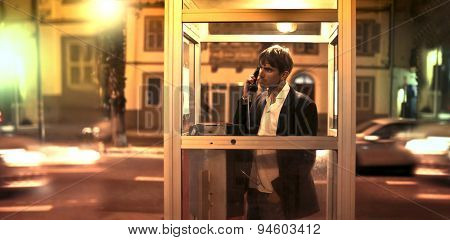 Man calling someone inside a phone box