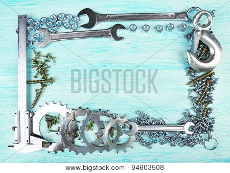 Screw nuts and wrenches frame, on color wooden background