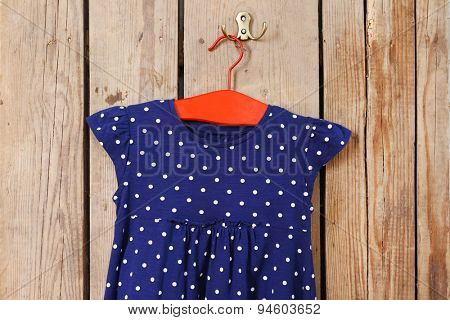 Child dress on hanger on wooden wall background