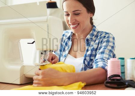 smiley young woman sewing yellow dress
