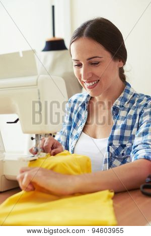 sempstress working with sewing machine and smiling