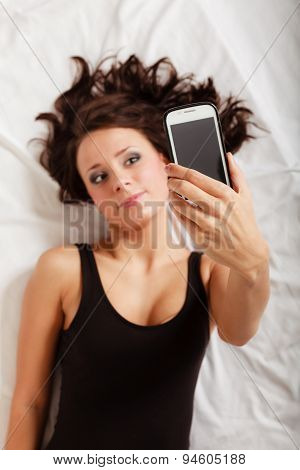 Sexy Lazy Girl Lying With Phone On Bed In Bedroom