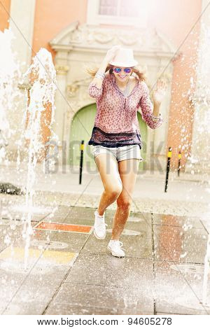 A picture of a happy woman running through the fountain