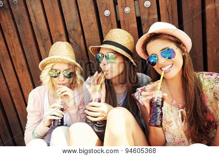 A picture of a group of girl friends drinking soda on the pier