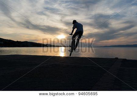 Silhouette of a bmx biker against the sun.