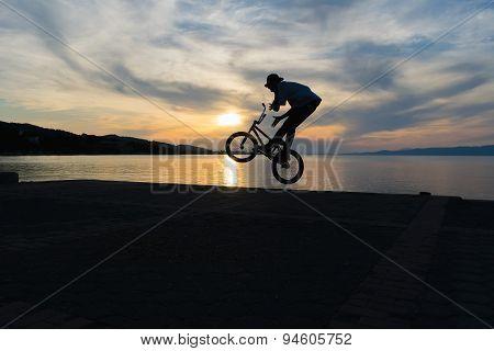 Bmx biker silhouette doing tricks against the sunset.
