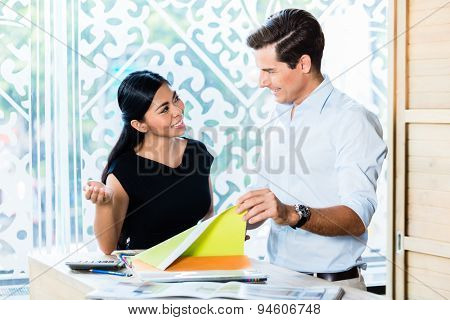 Mixed Asian Caucasian couple in furniture store or showroom choosing color and material for furnishing