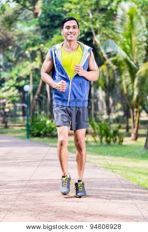 Asian man jogging or running in tropical park for fitness
