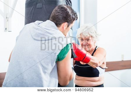 Senior woman with trainer in boxing sparring hitting sandbag