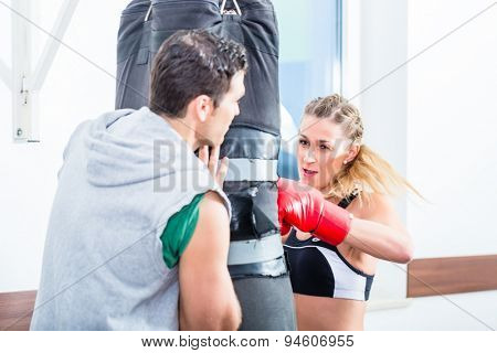 Young woman with trainer in boxing sparring hitting sandbag