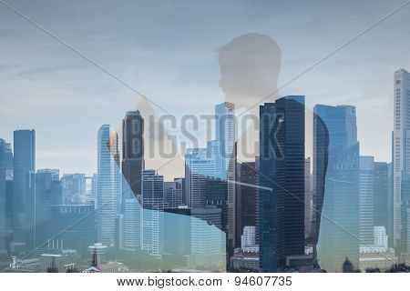 Double exposure of man with lap top on city background