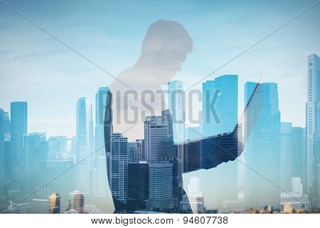 Double exposure of man with lap top on the blurred city background