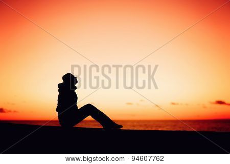 Silhouette of a woman sitting on the edge over beautiful red sunset
