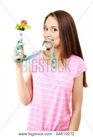 Healthy young woman with vegetables on fork and measuring tape isolated on white