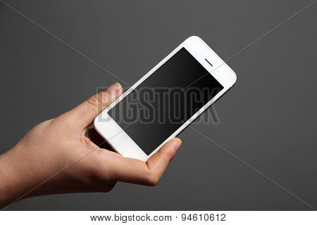 Hand holding mobile smart phone on gray background