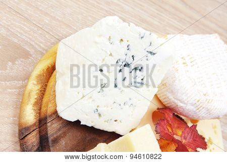 various types of cheese on wooden platter over wooden table