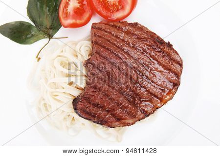 italian food : pasta with tomato on basil and roasted sirloin beef  steak on plate isolated over white background
