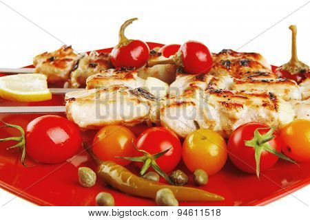 fresh grilled chicken shish kebab served with tomato cherry hot peppers on skewers over red plate isolated on white background