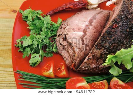 beef slice on red plate and vegetables on wood