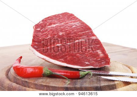 fresh raw beef meat steak chunk with red hot pepper on wood with stainless steel knife