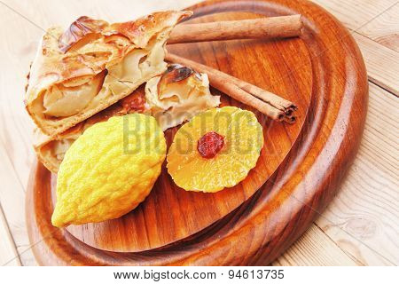 sweet apple cake with lemon and cinnamon sticks on wooden table
