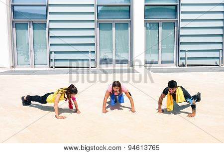 Group Of Young People Performing Pushups In Modern Urban Area - Fitness Girls Exercising With Coach