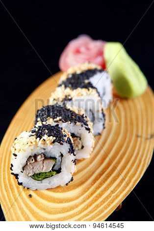 Maki sushi with sesame in a black background