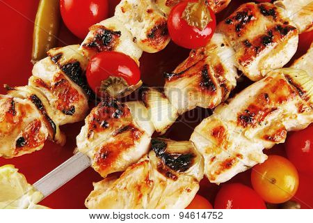 fresh grilled chicken shish kebab served wtih tomato cherry hot peppers on skewers over red plate isolated on white background