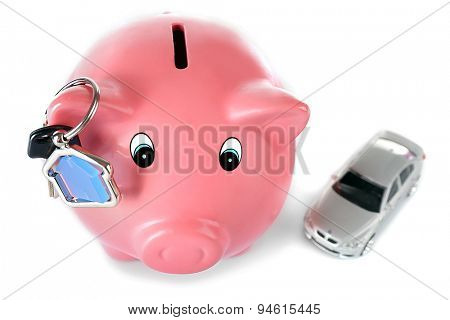 Piggy bank with toy car and key isolated on white