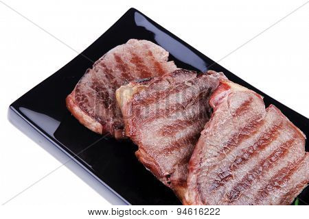 roasted beef meat steaks on black ceramic plate isolated over white background