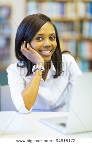beautiful young female african college student sitting in library