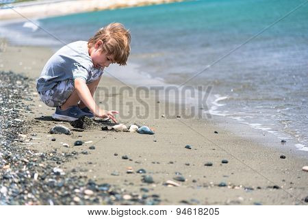 Boy Playing With Stones On A Beach